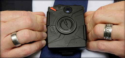 In this Feb. 19, 2015, file photo, Steve Tuttle, vice president of communications for Taser International, demonstrates one of the company's body cameras for The Associated Press during a company-sponsored conference hosted by Taser at the California Highway Patrol Headquarters in Sacramento, California. (AP Photo/Rich Pedroncelli)
